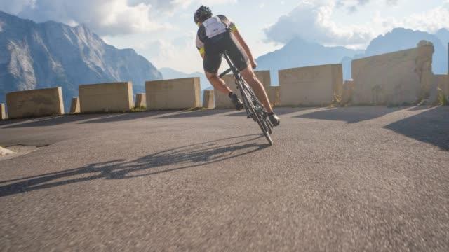 male road cyclist moving downhill scenic mountain road, going into a turn - ciclismo su strada video stock e b–roll