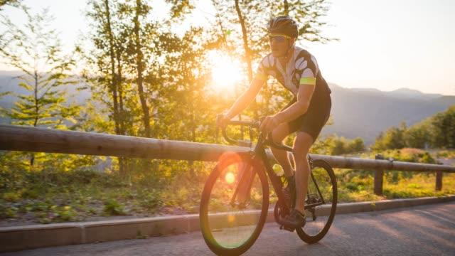 male road cyclist nearing the finish line - ciclismo su strada video stock e b–roll
