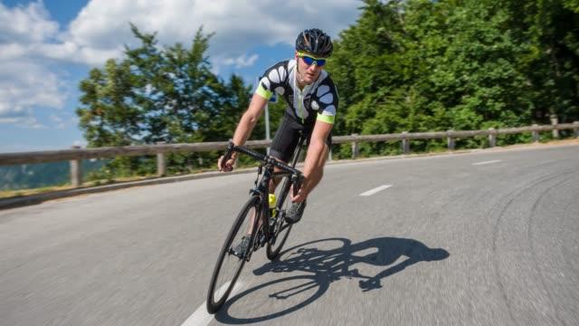 ciclista su strada maschio in discesa un passo di montagna - triatleta video stock e b–roll