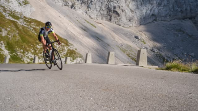 Male road cyclist speeding downhill