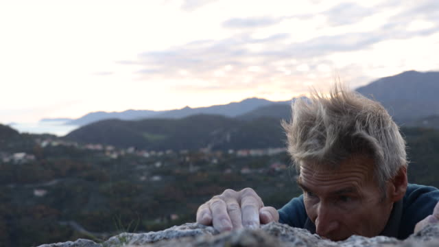 male rock climber grips rock holds at cliff edge, with chalk covered hands - cinquantenne video stock e b–roll