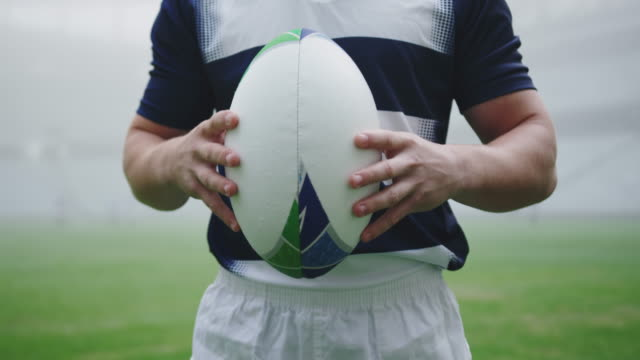 Male rugby player holding rugby ball in the stadium 4k Mid section of Caucasian male rugby player holding rugby ball in the stadium. Fog in the background 4k rugby stock videos & royalty-free footage