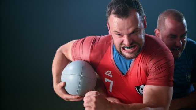 slo mo mężczyzna rugbysta trzyma piłkę i ucieka przed przeciwnikiem - trykot filmów i materiałów b-roll