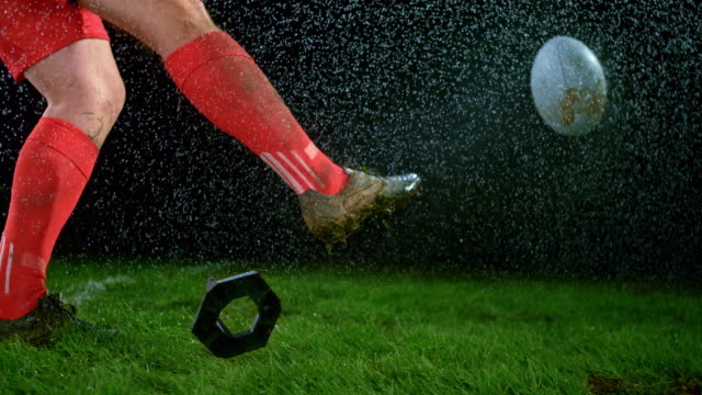 SLO MO Male rugby player in red outfit kicking the ball in pouring rain video