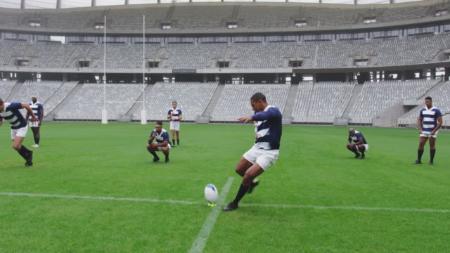 Male rugby player kicking rugby ball in ground at stadium 4k Front view of African American male rugby player kicking rugby ball in ground at stadium. They are smiling and celebrating 4k rugby stock videos & royalty-free footage