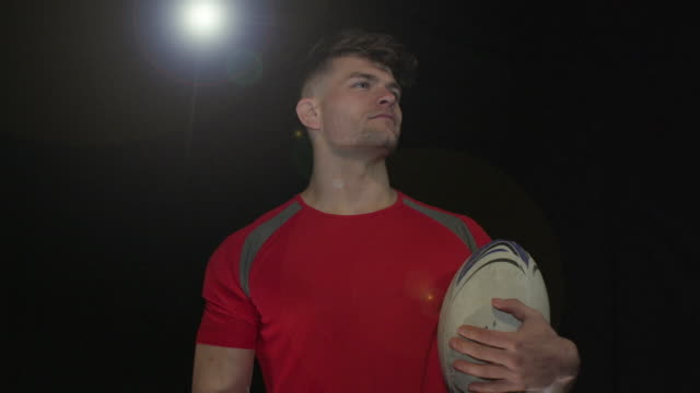 Male Rugby Player Portrait pose - Super Slow Motion 180 degree rotation Stock HD video clip footage of a male Rugby Player. Filmed in Super Slow motion, the camera rotates 180 degrees around the player. Black Background. Indoors pre game stock videos & royalty-free footage
