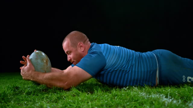 SLO MO Male rugby player scoring by grounding the ball over the opponents' goal-in area Slow motion medium shot of a male rugby player in blue grounding the ball across the opponents' goal line and scoring a point. Shot in Slovenia. rugby stock videos & royalty-free footage