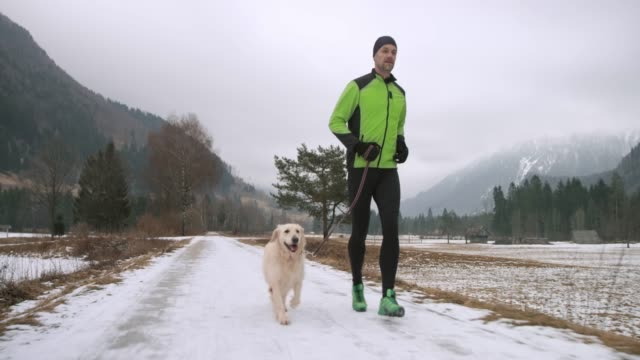Male runner and his dog running on a snowy walkway on a cold winter day