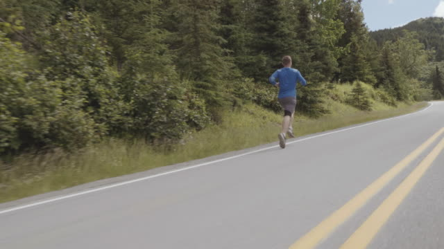 UHD 4K SLOMO: Male runner exercising on a scenic highway in the mountains video