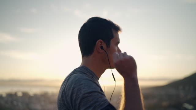 en manlig löpare sätta öronsnäckor i öronen innan jogging stående på bergets topp mot himlen vid sunrise-atlet redo för sin körning - jogging hill bildbanksvideor och videomaterial från bakom kulisserna