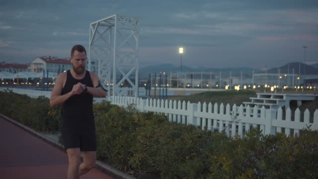 Male runner is training alone in evening time in darkness in city park video
