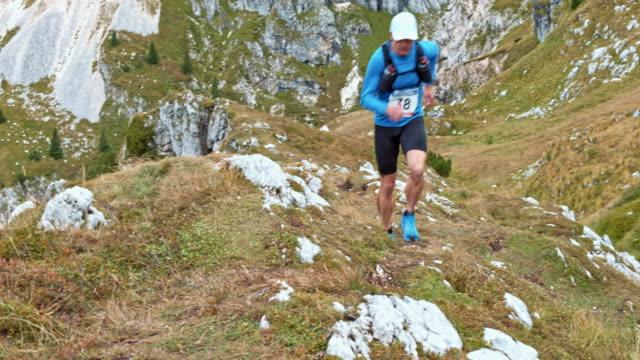 Hombre corredor maratón por una ladera herbosa - vídeo