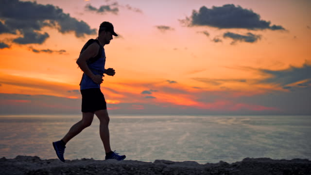 slo mo male runner running by the sea at sunset - triatleta video stock e b–roll
