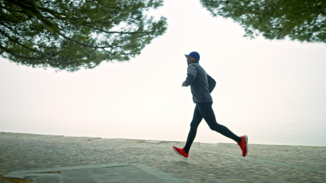 SLO MO TS Male runner running on a footpath along the beach on a foggy morning