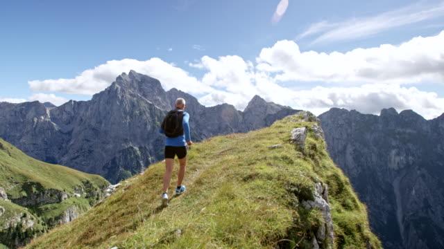 slo mo 남성 러너의 햇빛에 산 능선의 가장자리에 실행 - mountain top 스톡 비디오 및 b-롤 화면