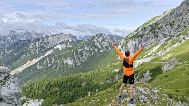 햇빛에 산 정상을 실행 하 고 높이 공중 남성 러너 승리에 손 - mountain top 스톡 비디오 및 b-롤 화면