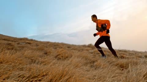 vídeos de stock e filmes b-roll de slo mo male runner running up the grassy slope - correr