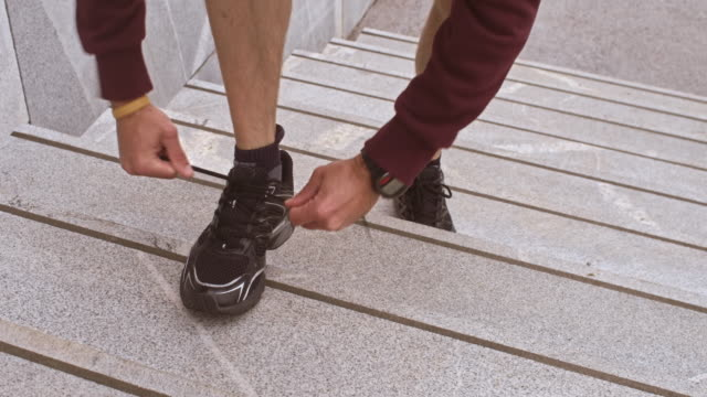 LD Male runner stopping on stairs to tie a shoelace video