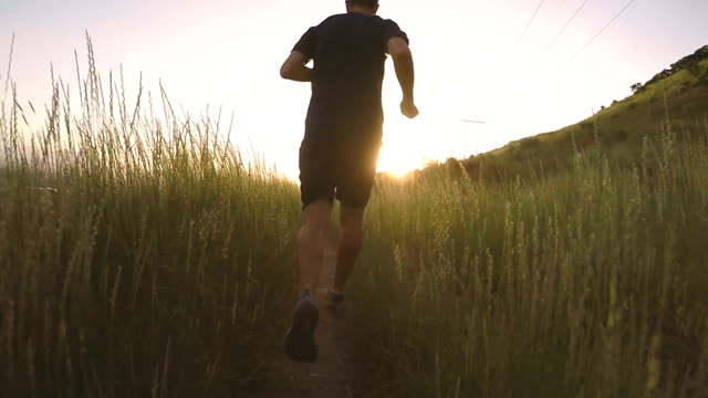 Male Running on Utah Mountain Trail A mid adult male is running along a mountain trail above Springville, Utah, USA. He runs into the sunset along the Bonneville Shoreline Trail enjoying his time in nature. Slow motion HD video. mid adult stock videos & royalty-free footage