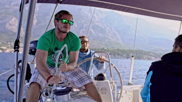 4K Male sailing team adjusting rigging on sailboat on sunny ocean, real time video