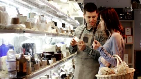 vidéos et rushes de assistante de vente mâle donnant des conseils aux clients femmes dans delicatessen shopping pour le fromage - client