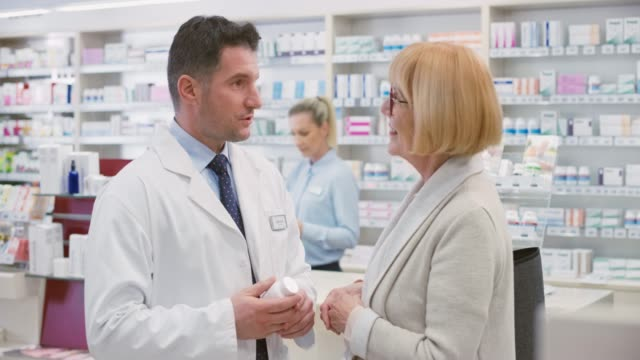Male salesperson advising a senior woman about a mineral supplement