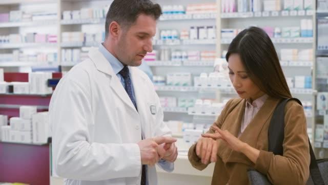 männliche verkäuferin, die ein bisschen lotion auf die hand einer asiatischen kundin legt - kosmetik beratung stock-videos und b-roll-filmmaterial