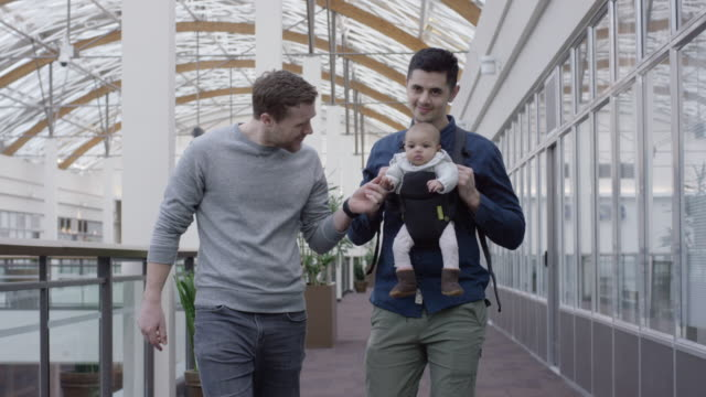 Male Same-Sex Couple Walking Indoors with Their Infant A male same-sex couple walks through a mall with their beautiful baby gay man stock videos & royalty-free footage