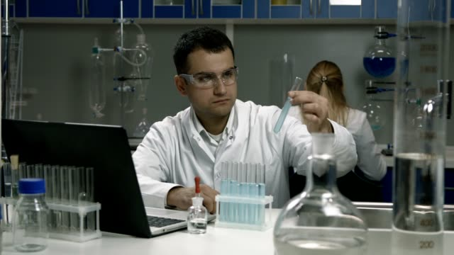 Male scientist working with tubes in laboratory video
