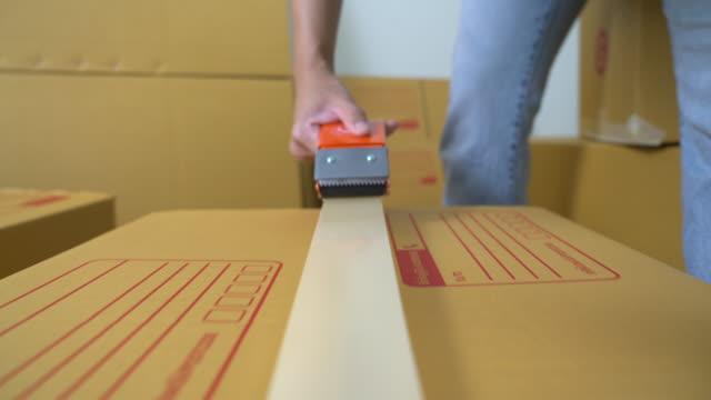 male sealing big box with tape for moving - attività fisica video stock e b–roll