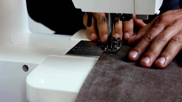 männliche näherin haltetuch hinter nähmaschine - kurzwaren stock-videos und b-roll-filmmaterial