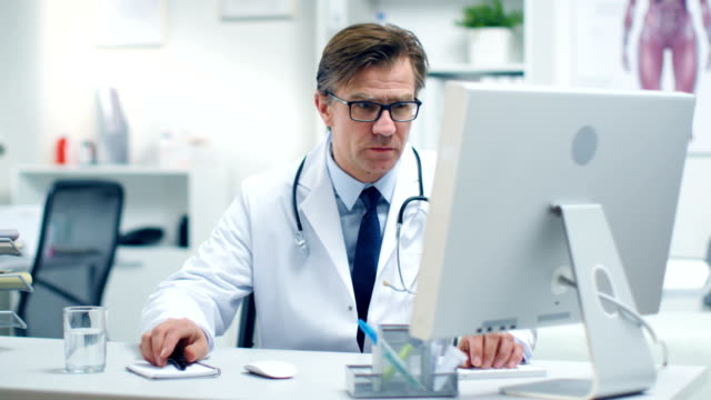 male senior doctor working at his desk on a personal computer. his office is white, bright and modern. - ambulatorio medico video stock e b–roll