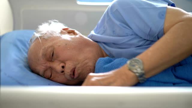 vídeos y material grabado en eventos de stock de paciente masculino senior tos en cama de hospital - flu