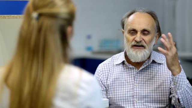 männlicher senior patient besuch eines arztes im krankenhaus - medizinexamen stock-videos und b-roll-filmmaterial