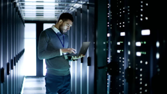 male server engineer in data center. he stands before open door of rack server and works on his laptop. - supporto tecnico video stock e b–roll