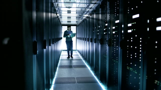 Male Server Engineer Walks with Laptop Through Working Data Center Full of Rack Servers. Male Server Engineer Walks with Laptop Through Working Data Center Full of Rack Servers. Shot on RED EPIC-W 8K Helium Cinema Camera. supercomputer stock videos & royalty-free footage