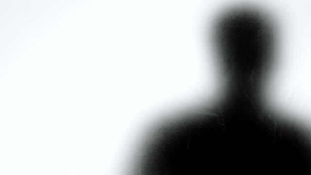 Male shadow looking through glass widow, burglar planning crime, psychopath