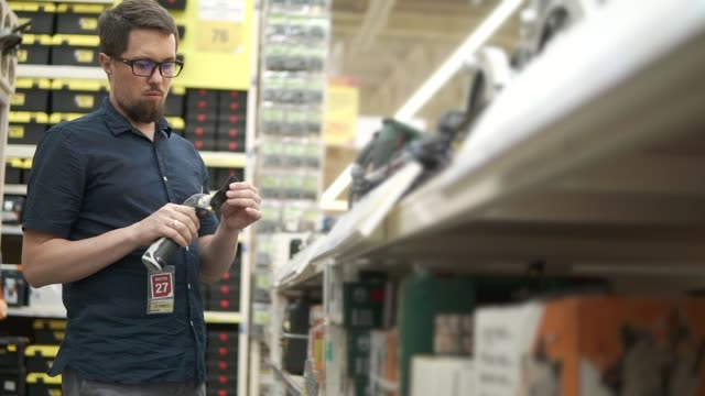 Male shopper is taking oscillating power tool in a shop of building tools Man is taking in hands a multi-tool in a trading hall in hypermarket. He is looking on it and trying weight and usability power tool stock videos & royalty-free footage