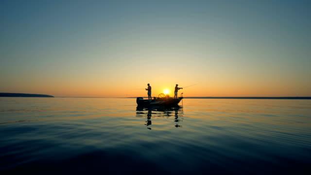 日の出の間にモーターボートから釣りながら男性のシルエット - 漁師 外人点の映像素材/bロール