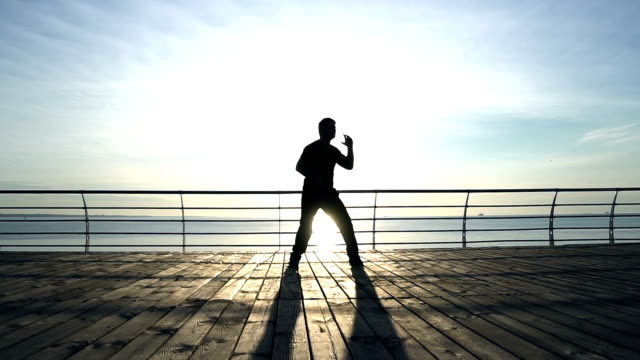 男性 sillhouette はスローモーションでサンライズに対して訓練が戦う ビデオ
