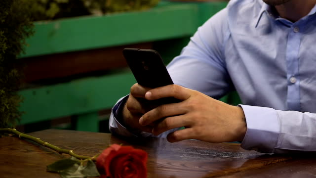 Male sitting at table using cellphone, red rose lying in front, waiting for date video