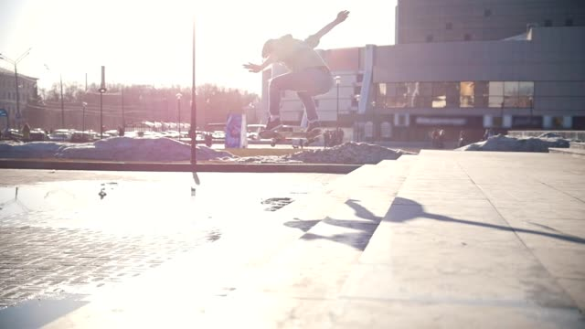 晴れた日の屋外の階段をジャンプ男性のスケートボーダー - スケートボードをする点の映像素材/bロール