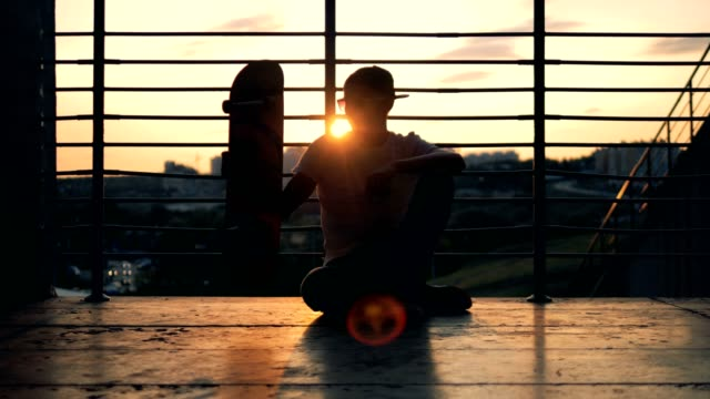 Male skater is sitting on the ground and relocating his skateboard