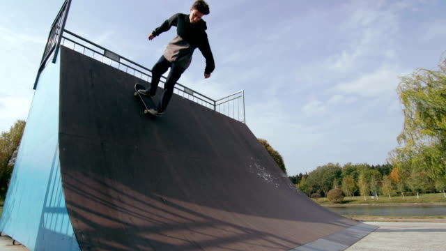 Male skater make turns in ramp in wooden skatepark, wide angle view in slowmotion