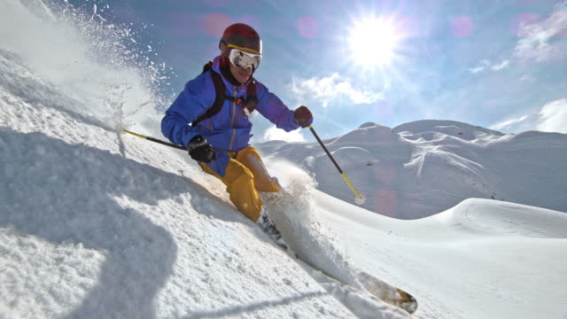 slo mo male skier riding off piste on a sunny mountain - sci sci e snowboard video stock e b–roll