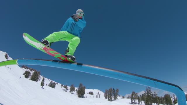 niedrigen winkel: männliche snowboarder rutschen nach unten ein metallgeländer in einem malerischen skiort. - grind stock-videos und b-roll-filmmaterial