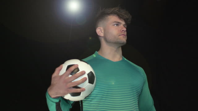 Male Soccer / Football Player Portrait pose - Super Slow Motion 180 degree rotation Stock HD video clip footage of a male Soccer / Football Player. Filmed in Super Slow motion, the camera rotates 180 degrees around the player. Black Background. Indoors pre game stock videos & royalty-free footage