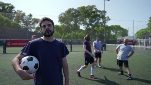 Male soccer player standing on soccer field and holding ball in his arm Portrait of Mid adult men standing on soccer field while other teammates doing pregame routine pre game stock videos & royalty-free footage