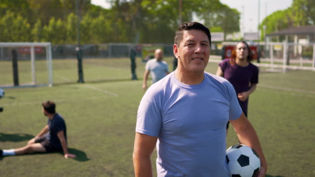 Male soccer player standing on soccer field and holding ball in his arm Portrait of mature men standing on soccer field and looking at camera while his teammates doing pregame routine pre game stock videos & royalty-free footage