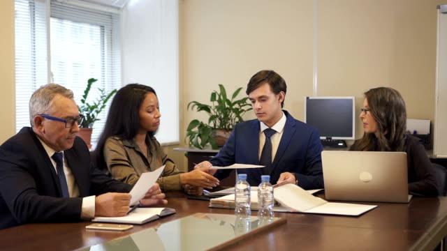 vídeos y material grabado en eventos de stock de abogado masculino dando borrador de contrato a empresario maduro y empresaria afroamericana - abogado